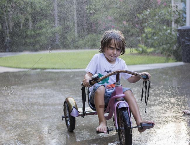 5 year old boy riding his tricycle bike in the rain