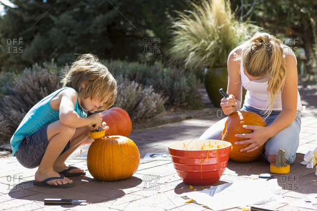 Young boy and his sister carving pumpkins