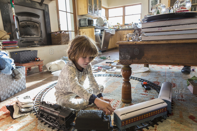 4 year old boy wearing pajamas playing with toys at home