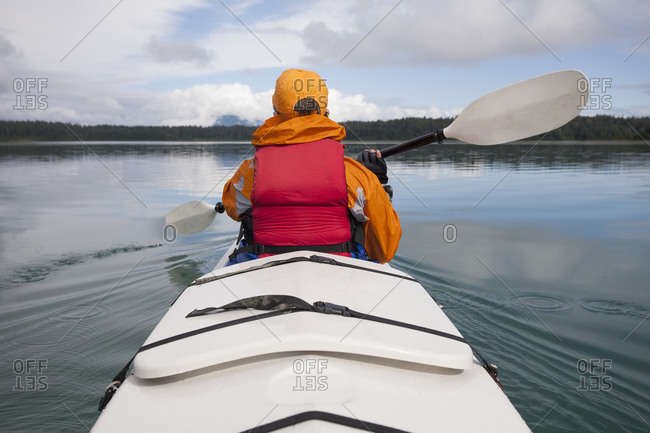 Woman sea kayaking calm waters of an inlet in a national park.