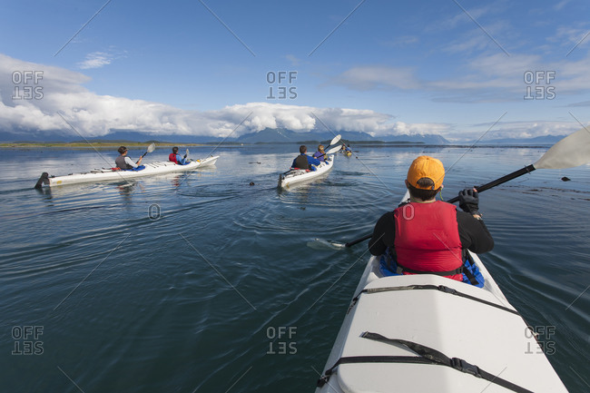 A small group of people kayaks in pristine waters of an inlet on the Alaska coastline.