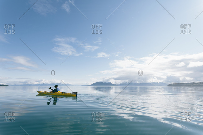 Man sea kayaking on sunny day in an inlet on the Alaska coastline.