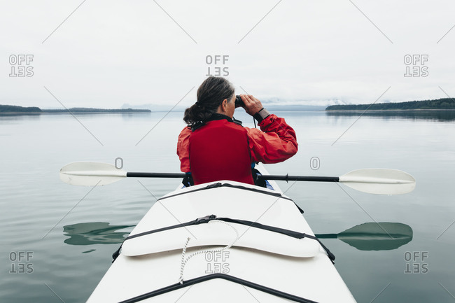 Sea kayakers looking at nautical chart and map, an inlet on the Alaska coastline.