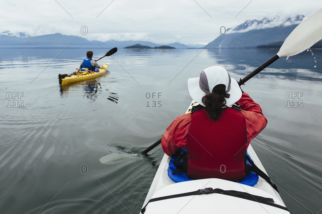 A small group of sea kayakers paddle pristine waters of Muir Inlet in Glacier Bay National Park, Alaska