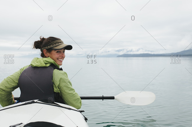 Happy female woman sea kayaking pristine waters of Muir Inlet in Glacier Bay National Park and Preserve, Alaska