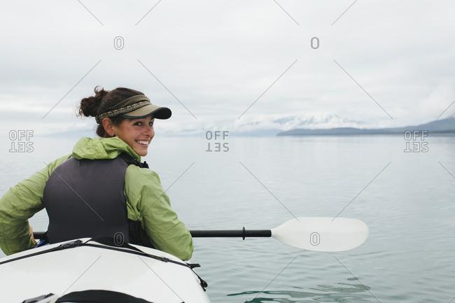 Happy female woman sea kayaking pristine waters of Muir Inlet in Glacier Bay National Park and Preserve, Alaska
