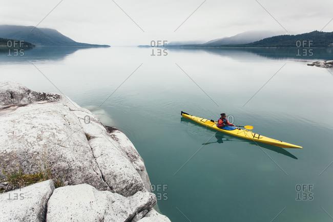 Female sea kayaker paddling pristine waters of Muir Inlet, overcast sky in distance, Glacier Bay National Park, Alaska