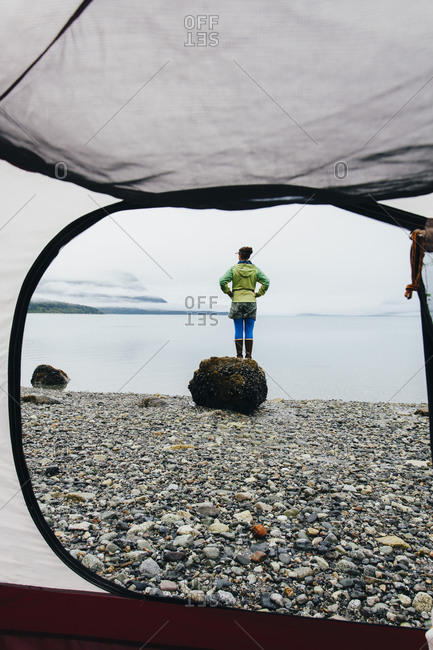 View through camping tent doorway of woman standing on beach, an inlet on the Alaska coastline.