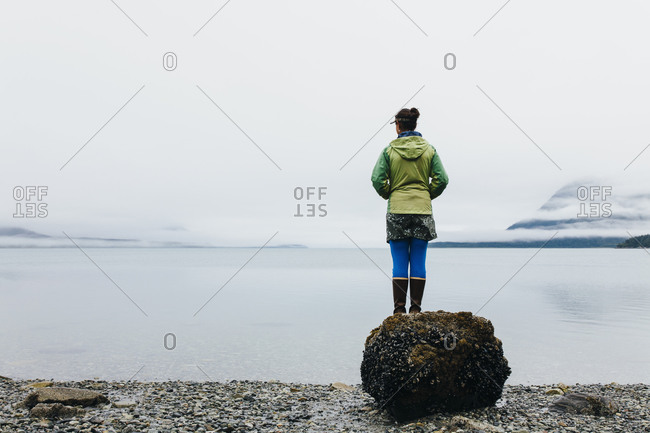 Woman standing on a beach looking out a coastal inlet, mist and low cloud.