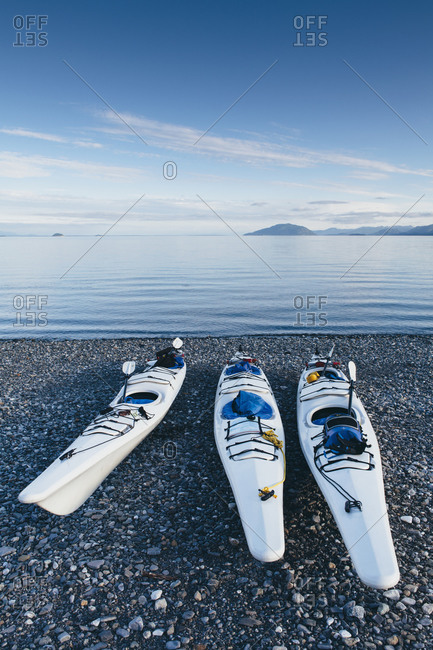 Sea kayaks on remote beach, calm waters of Muir Inlet in distance,, Glacier Bay National Park and Preserve, Alaska