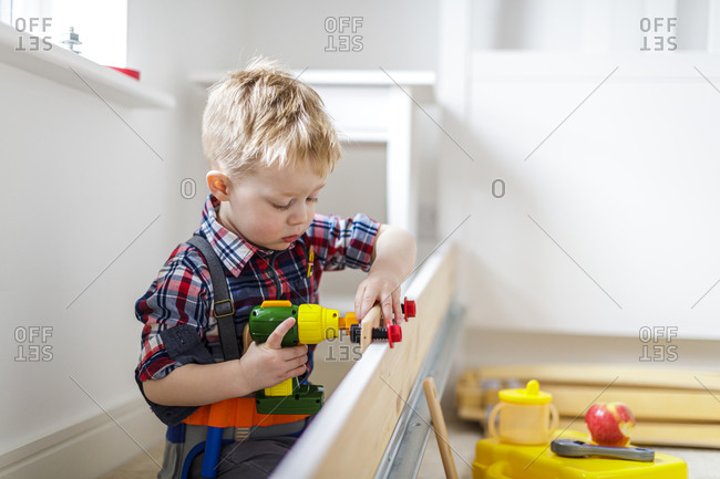Young boy using toy power tool at home