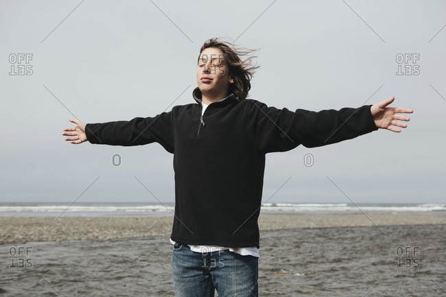 Teenage boy on beach with arms outstretched towards breeze, ocean in distance