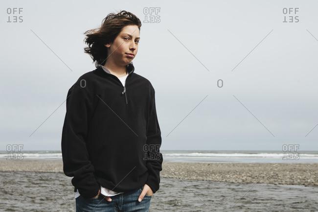 Portrait of moody teenage boy on beach