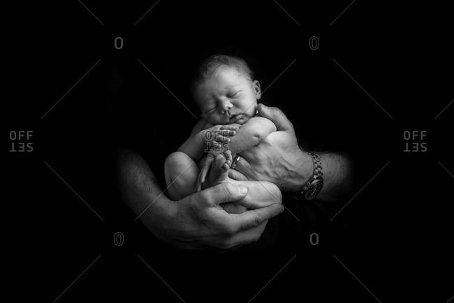 Sleeping newborn baby being held in hands of father