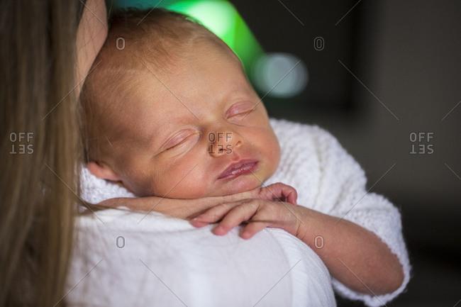 Portrait of baby asleep on mother's shoulder