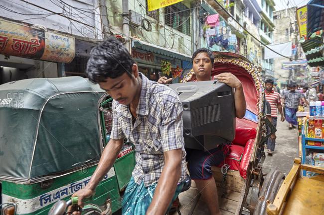 Dhaka, Bangladesh - April 28, 2013: Man carrying a television set while riding on tuk tuk at Hindu Street/Shankaria