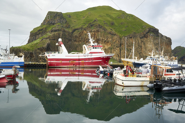 Vestmannaeyjar, Heimaey, Iceland - July 19, 2019: Boats in the Heimaey Harbour fishing port on Heimaey in Westman Islands with Heimaklettur in the background