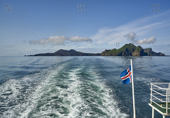 View of the steep cliffs and the entrance of the fjord on Heimaey island, seen from the back of a ferry with an Icelandic flag, Vestmannaeyjar, Heimaey, Iceland