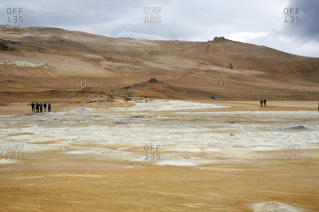 Tourists visiting the Hverir geothermal spot with mud pools and steaming fumaroles emitting sulfuric gas in Iceland