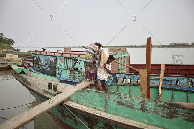 Bangladesh - April 26, 2013: Workers carrying good onto boat on the Padma river