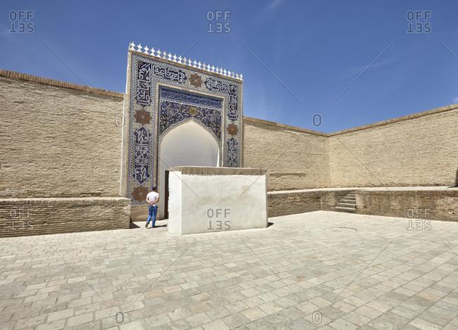 Bukhara, Uzbekistan - May 19, 2016: Tourist man at the Ark of Bukhara fortress