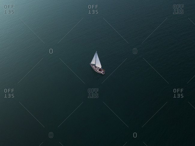 Aerial view of a solitary yacht sailing through the bay in a cloudy summer afternoon, Studland Bay, Dorset, England.