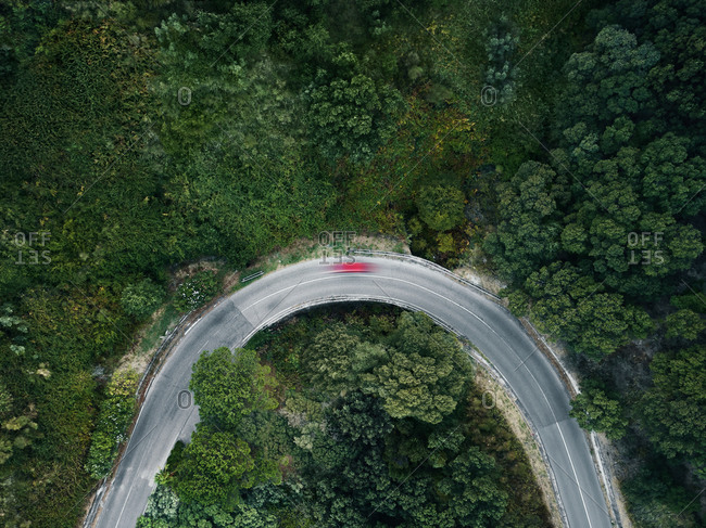 Aerial view of a single red car traveling fast on a road in the woods, Petrizzi, Calabria, Italy.