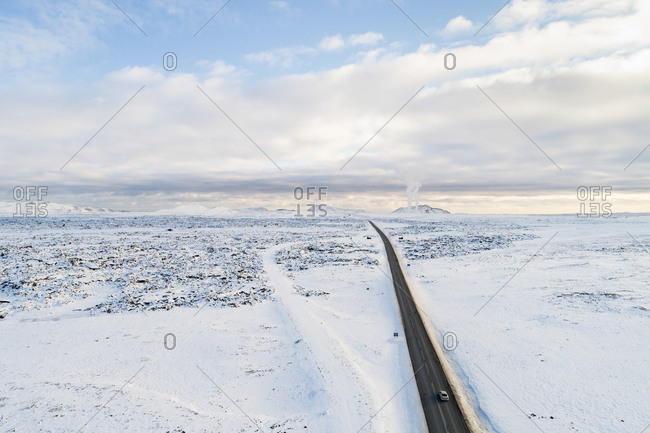 Aerial winter view of road to Grindavik and Blue Lagoon, through lava field covered with snow, with steam plumes of the Svartsengi geothermal power plant, Reykjanes, Iceland