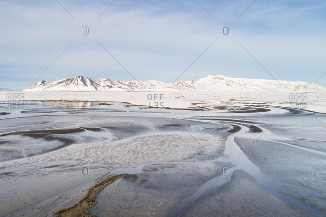 Aerial view of sandbanks in the estuary Leirarvogur, in front of snow-covered mountains in winter, western Iceland
