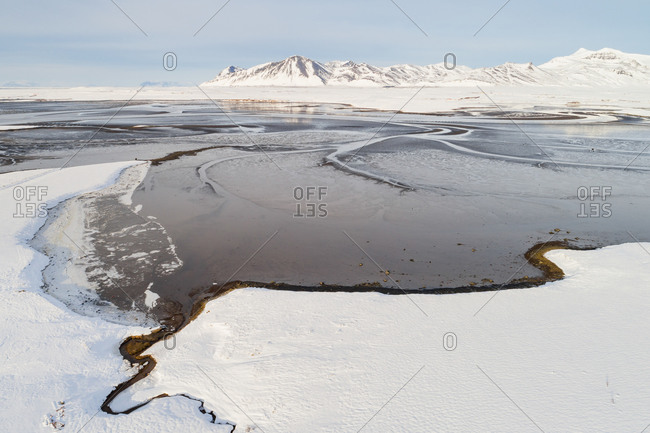 Aerial view of the estuary Leirarvogur, in front of snow-covered mountains in winter, western Iceland