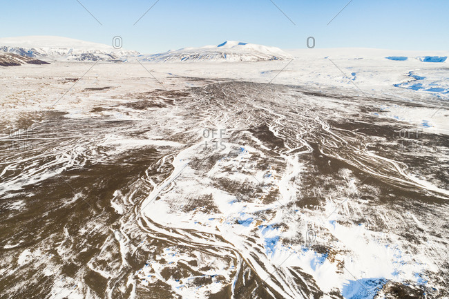 Aerial view of amazing trails of snow in Geitlandsrhaun lava field in front of Langjökul glacier and Hafrafell mountain, western Iceland