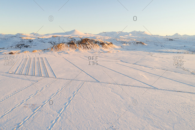 Aerial winter view of the first sunlight of the day over fields covered with snow in front of mountains, Snaefellsnes, western Iceland