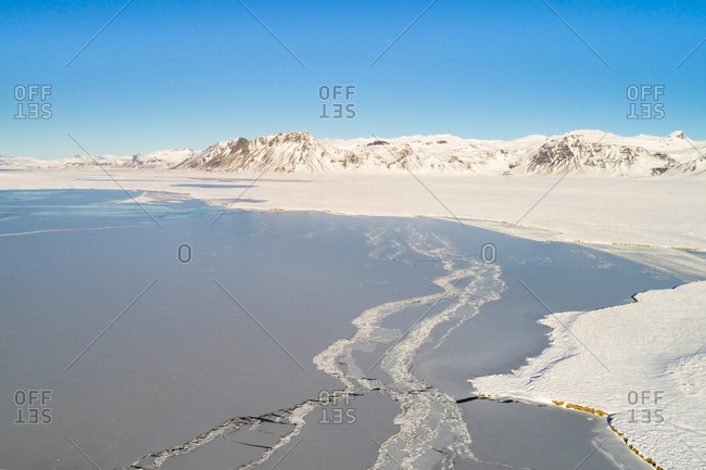 Aerial view of frozen lake, surrounded by snow-covered land and mountains on a  cold and sunny day in winter, Snaefellsnes, Iceland