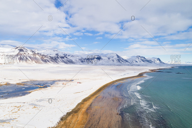 Aerial view of beach along land and mountains covered with snow during winter in Snaefellsnes, Iceland