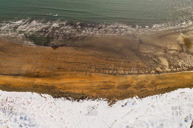 Abstract aerial view of beach along land covered with snow during winter in Snaefellsnes, Iceland