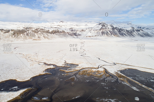 Aerial view of estuary with sandbanks near Budir, in front of snow-covered land and mountains in winter, Snaefellsnes, western Iceland