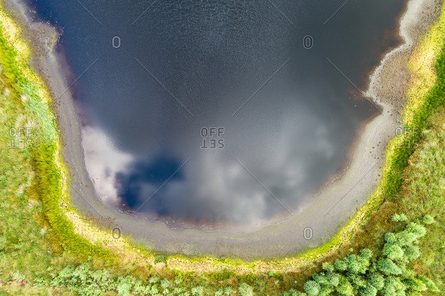 Abstract aerial view of partly dried out lake shaped like a cup with reflection of the sky, Engbertsdijksvenen, Twente, Netherlands