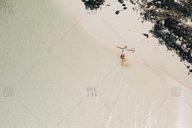 Aerial view of beautiful woman swimming and sunbathing in Atlantic ocean lagoon beach, Fuerteventura, Canary islands.