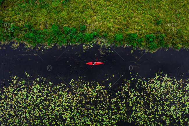 Aerial view of travel person paddling in wild river with red kayak, shot in Labanoras, Lithuania.