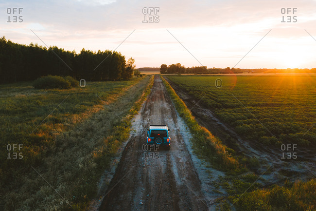 Aerial view of 4x4 suv vehicle driving on gravel countryside road during summer time sunset in Svencele, Lithuania.