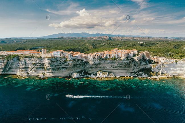 Aerial view of a yacht cruising along the cliffs of Bonifacio, Corsica, France.