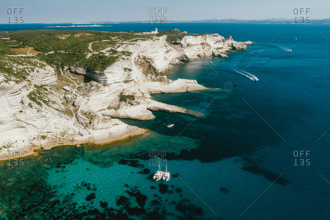 Aerial of catamarans anchored in front of the cliffs at Bonifacio, Corsica, France.