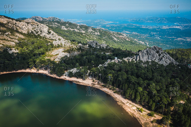 Aerial view of lake de  with the Mediterranean Sea in the background in between the mountains of Agnarone, Corsica. France.