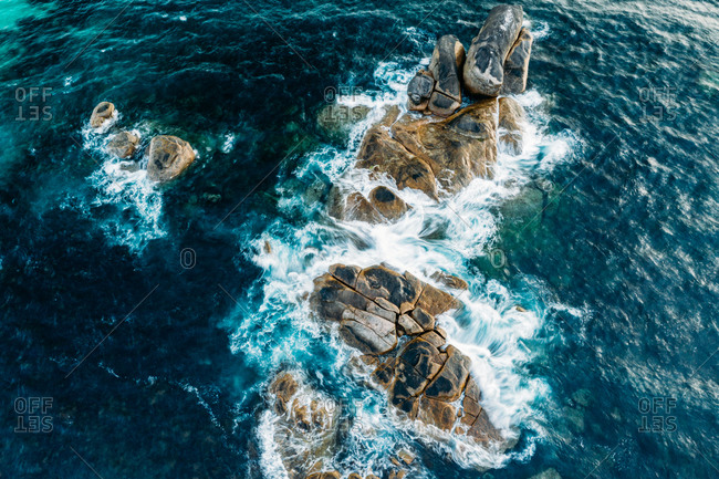 Aerial view of water splashing on rocks at Redgate Beach, Western Australia.