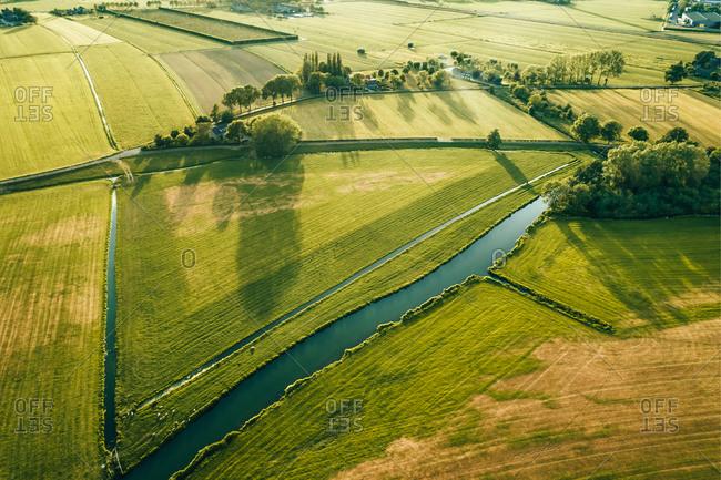 Aerial view of a river running through the idyllic farmlands in IJsselstein, Utrecht, The Netherlands.