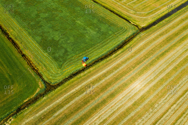 Aerial view of tractor mowing the grass on farmland in Friesland, The Netherlands.
