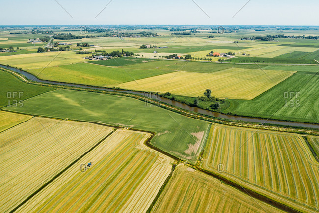 Aerial view of farmland with farmer houses in Friesland, The Netherlands.