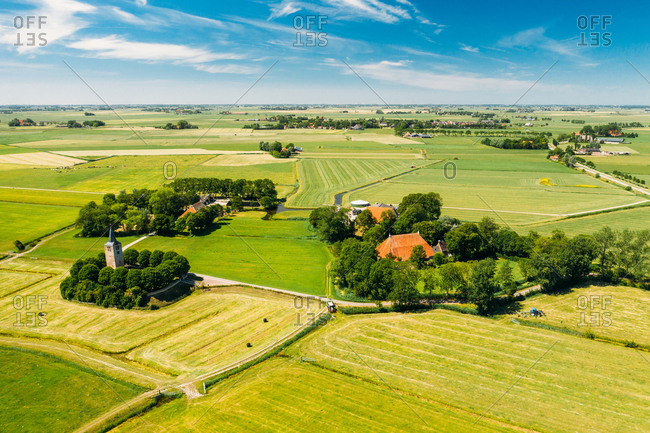 Aerial view of tractor mowing the grass on farmland with farmer houses and a little church in Friesland, The Netherlands.