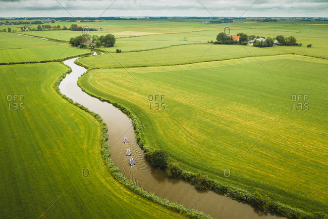 Aerial view of solar panel boats navigating through the farmlands in Bolsward, Friesland, The Netherlands.