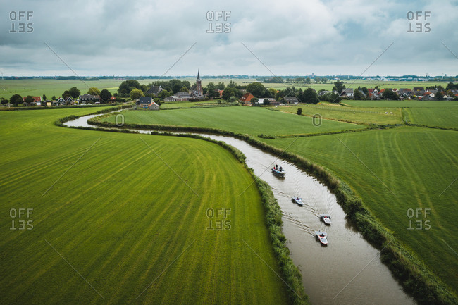 Aerial view of solar panel boats navigating through the farmlands of Schettens, Friesland, The Netherlands.